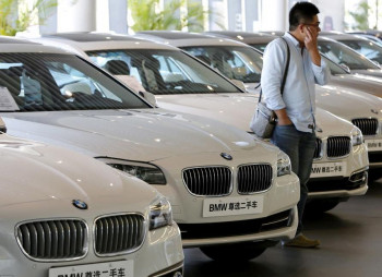 FILE-PHOTO-A-man-takes-a-look-at-second-hand-BMW-cars-at-a-dealer-shop-in-Beijing